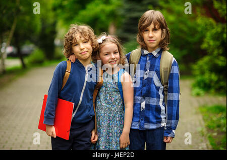 Three little school students, two boys and the girl, stand in an embrace on the schoolyard. Children's friendship. - Stock Photo