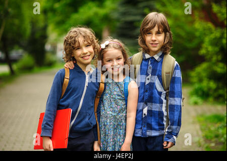 Three little school students, two boys and the girl, stand in an embrace on the schoolyard. Friends smile. School - Stock Photo