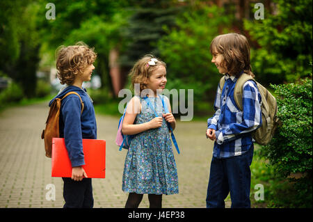 Cute little school students briskly talk on the schoolyard. Children have a good mood. Warm spring morning. Behind - Stock Photo