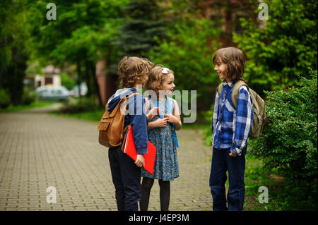 Little school students briskly talk on the schoolyard. Children have a good mood. Warm spring morning. Behind shoulders - Stock Photo