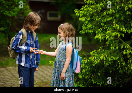 Two little school students, the boy and the girl, cheerfully communicate on the schoolyard. Behind shoulders at - Stock Photo