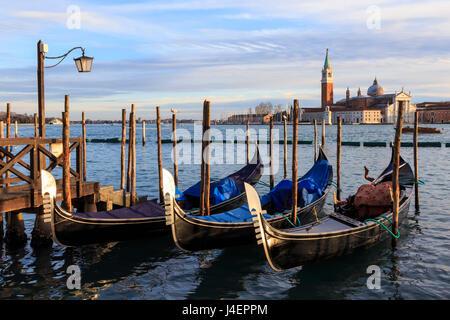 Gondolas, San Marco waterfront at sunset in winter, view to San Giorgio Maggiore, Venice, UNESCO, Veneto, Italy - Stock Photo