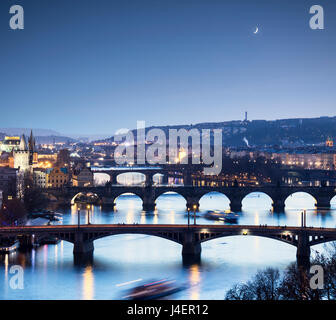 Dusk lights up the historical bridges and buildings reflected on Vltava River, Prague, Czech Republic, Europe - Stock Photo