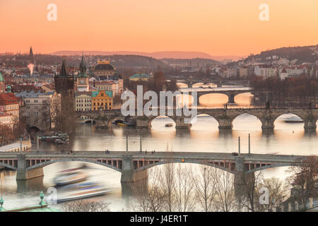 Orange sky at sunset on the historical bridges and buildings reflected on Vltava River, Prague, Czech Republic, - Stock Photo