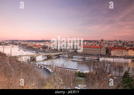 Pink sky on historical bridges and buildings reflected on Vltava River at sunset, Prague, Czech Republic, Europe - Stock Photo