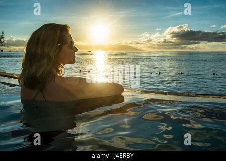 Woman enjoying the sunset in a swimming pool with Moorea in the background, Papeete, Tahiti, Society Islands - Stock Photo