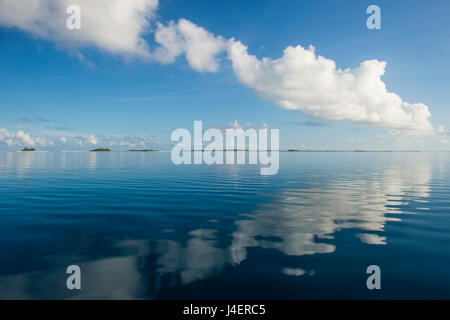 Clouds reflecting in the calm waters of Tikehau, Tuamotus, French Polynesia, Pacific - Stock Photo
