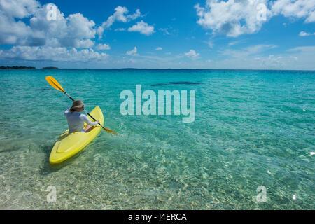 Woman kayaking in the turquoise waters of Tikehau, Tuamotus, French Polynesia, Pacific - Stock Photo