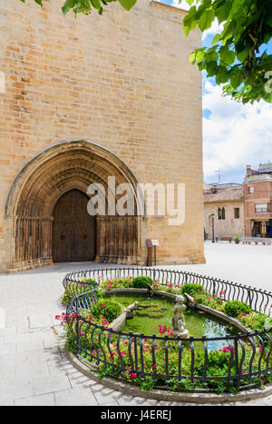 Ornamental fountain pond and double wooden doors  below archivolts on the facade of the Gothic Esglesia Vella de - Stock Photo