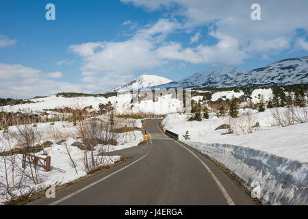 Road leading through the snow capped mountains of the Daisetsuzan National Park, UNESCO, Hokkaido, Japan - Stock Photo