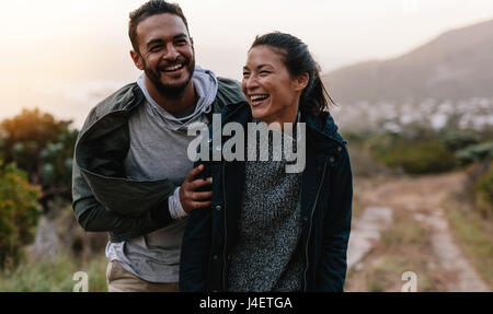 Portrait of couple walking through pathway on mountain. Man and woman enjoying vacation in countryside. Young people - Stock Photo