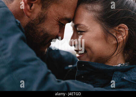 Close-up side portrait of young mixed race couple in love. Romantic couple embracing each other and smiling. - Stock Photo