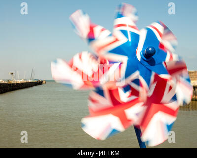 Pin wheel, toy windmill with the union jack flag colors on a sunny day. Brexit. - Stock Photo