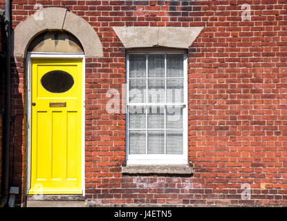 Yellow front door of an old traditional English terraced house. Canterbury, England. - Stock Photo