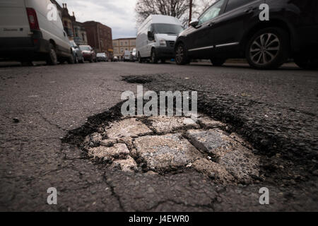 A large pot hole revealing underlying bricks on a road in Bristol. - Stock Photo