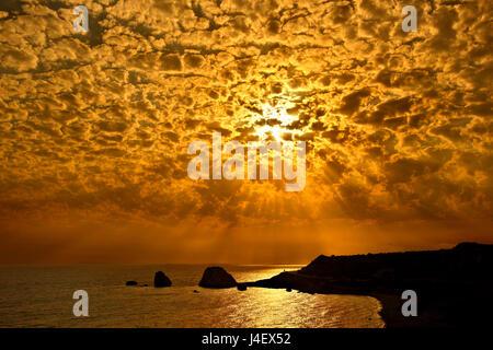Sunset at 'Petra tou Romiou' ('Greek's Rock', also known as 'Aphrodite's Rock' or 'Aphrodite's beach'), the 'birthplace' - Stock Photo