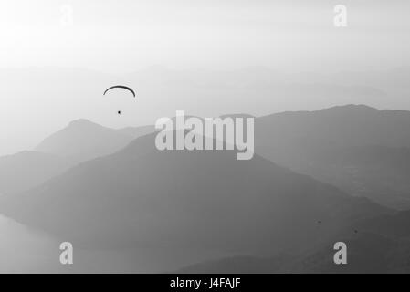 Paragliding over the mountains and the sea - Stock Photo