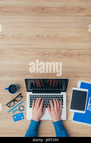 Businessman working at desk with a laptop and using a credit card, top view - Stock Photo
