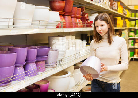 Teen girl Buys Ceramic flower pots at the shop - Stock Photo