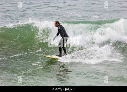 Surfer riding a wave enjoying the surf on a lovely sunny day at Bournemouth beach on Bank Holiday Monday in May - Stock Photo