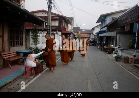 Thai people put food offerings to monks procession walk on the road of tradition of almsgiving with sticky rice - Stock Photo
