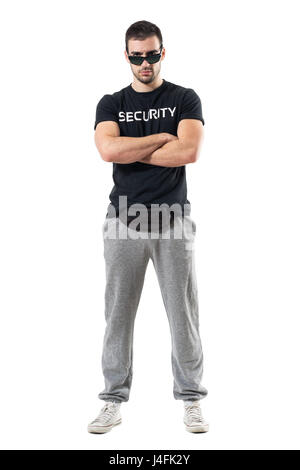 Tough serious bouncer or bodyguard with crossed arms staring at camera. Full body length portrait isolated on white - Stock Photo