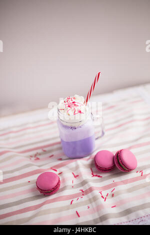 Purple coffee in stylized mason jar cup with macarons and roses and colorful decoration. Blueberry milk shake. Unicorn - Stock Photo