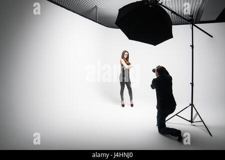 Girl the photographer takes pictures of model in black on a white background in Studio - Stock Photo