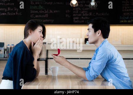 Asian man showing an engagement ring diamond to his amazed girlfriend in a restaurant. Proposal concept - Stock Photo