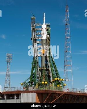 Gantry arms close around the Soyuz MS-04 spacecraft rocket to secure its vertical position on the Baikonur Cosmodrome - Stock Photo