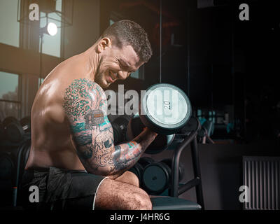 Very power athletic guy bodybuilder , execute exercise with dumbbells, in dark gy, - Stock Photo