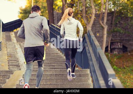 couple running upstairs in city park - Stock Photo