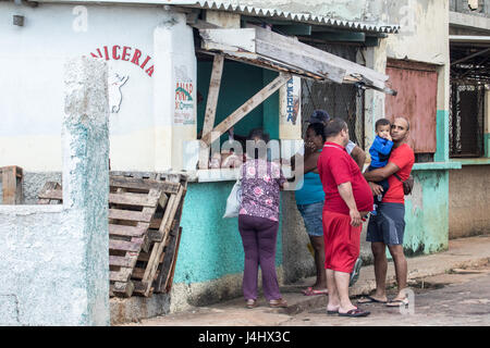 Cubans lining up to buy from a store on a side street in Havana - Stock Photo