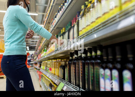 woman choosing olive oil at supermarket or grocery - Stock Photo