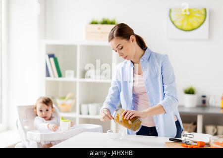 mother with blender cooking baby food at home - Stock Photo