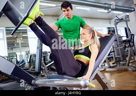 A girl is doing exercises on the foot simulator with  personal t - Stock Photo