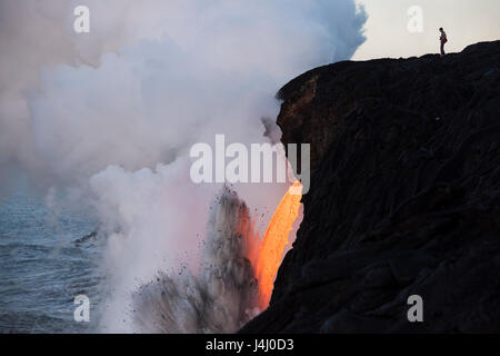 an unauthorized hiker in a restricted zone steps out onto an unstable sea cliff over a lava tube where hot lava - Stock Photo