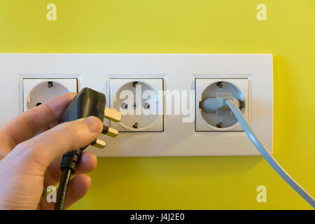 A concept shot of someone holding a British 3 pin plug which is incompatible with European type sockets. Britain. - Stock Photo