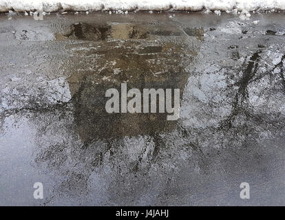 Puddle with reflection of a large brick home on the asphalt, trees next to the house and the edge of the white snow - Stock Photo