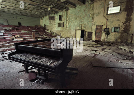 Old ruined grand piano in a concert hall in the city of Pripyat: collapsed rows of chairs, green walls, a broken - Stock Photo