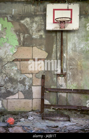Sports hall in the ruined abandoned school in the city of Pripyat: peeling walls, a basketball shield, on an dirty - Stock Photo
