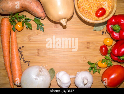 ingredients for lentil soup on a wooden board with copy space in the center - Stock Photo