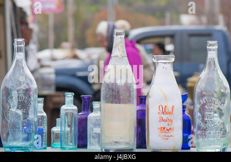 Close up of old colored glass bottles at an outside antique store. Stock Photo