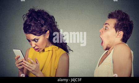 Shocked scared man looking at his upset mad girlfriend who is spying on his mobile phone - Stock Photo
