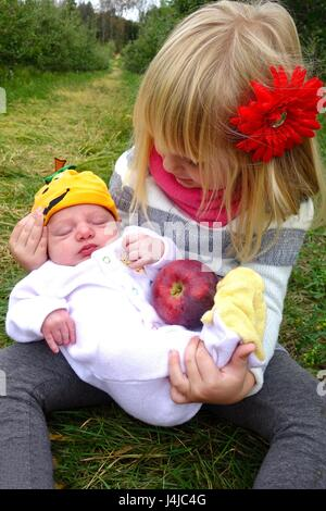 big sister holding new baby brother - Stock Photo