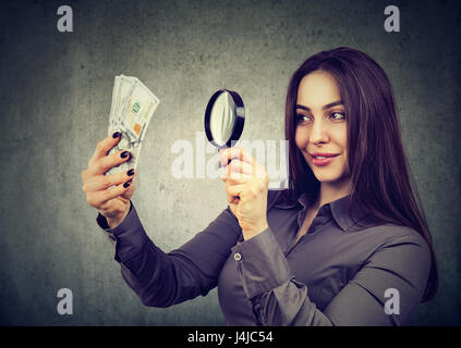 Young woman looking at one hundred dollar bills through magnifying glass - Stock Photo