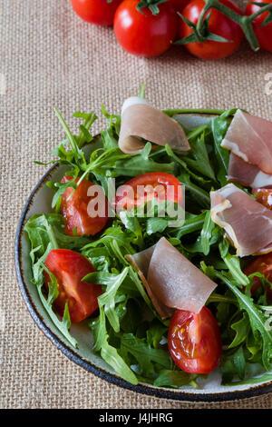 fresh healthy ruccola salad with tomato and ham - Stock Photo