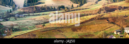 Small village on alpine hills in spring. Spring panoramic landscape of sunny alpine morning. mountain village spring - Stock Photo