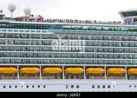 Passengers stand atop Royal Caribbean's MS Navigator of the Seas as it departs Southampton - Stock Photo