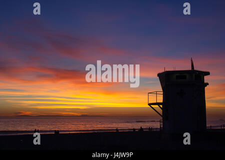 silhouette of people and lifeguard station watching a sunset over Laguna beach, California - Stock Photo